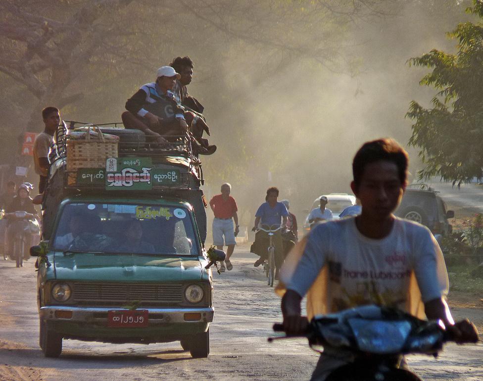 """Jobbkormányos autóval az út jobb oldalán – megszokott, sőt, szabályos közlekedési alaphelyzet ez Burmában. Az utakon a """"Jobbra tarts!"""" érvényes, ugyanakkor az autók nagy része Thaiföldről, Indiából, Japánból származó, agyonhasznált, olcsó jobbkormányos típus. A Bagan környékén készült képen együtt láthatjuk a közlekedés három tipikus eszközét, a biciklit, a robogót és a pickupot."""