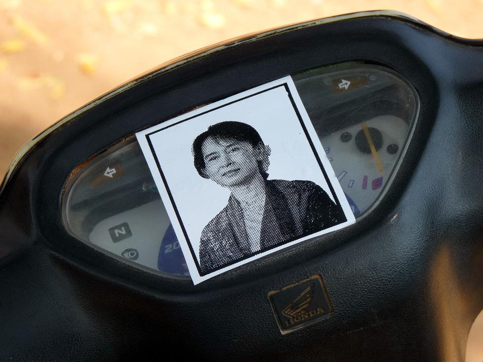 Változó idők. A robogón Ang Szan Szú Kji ellenzéki vezető fotója. A Nobel-békedíjas politikusnő hosszú időt töltött a katonai kormányzat börtöneiben és házi őrizetben. 1990-ben betiltott pártjának működését néhány éve engedélyezték újra, és a 2010-es választáson a parlamentbe is bejutott. Ang Szan Szú Kji a diktatúrával szembeni ellenállás vezetője és szimbóluma, korábban egy ilyen kép nyilvános mutogatásáért még letartóztatták volna a tulajdonosát.