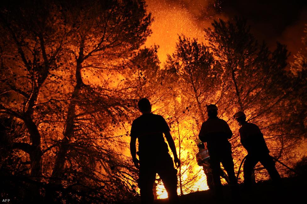 Tűzoltók próbálják megfékezni a lángokat a spanyol Macane hegyen, Alicante város közelében augusztus 13-án.
