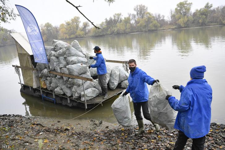 Önkéntesek PET-palackokkal töltött zsákokat pakolnak le egy kishajóról a Tisza partján, Tiszaszőlős közelében, 2020. november 11-én