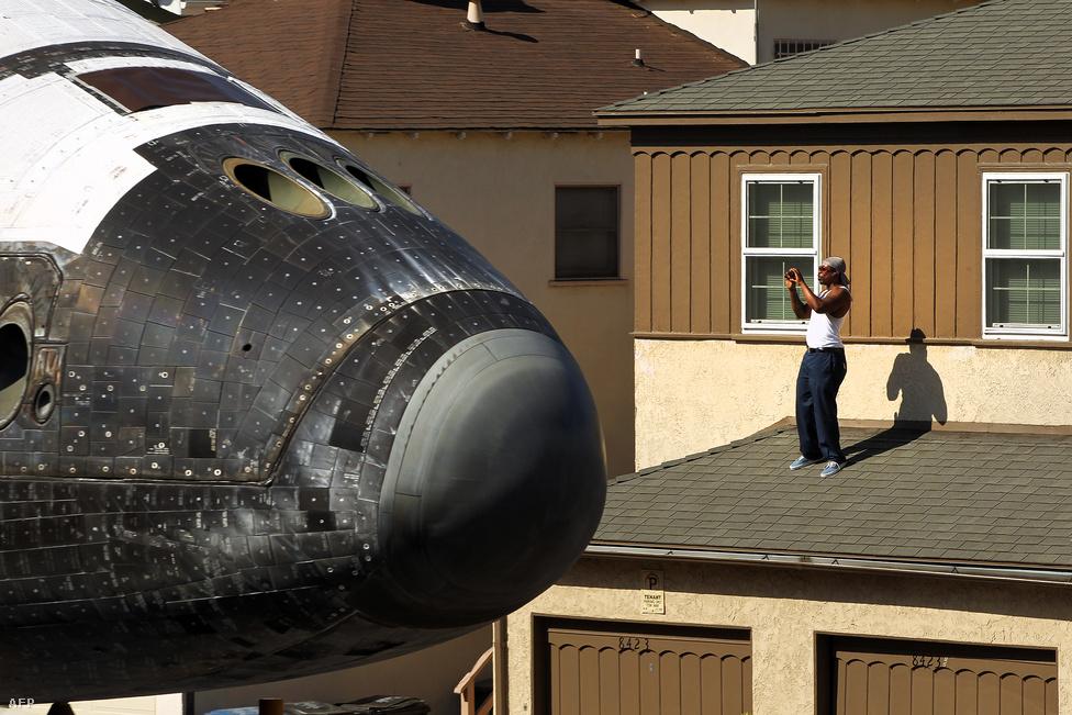 Háza tetejéről fotózza az Endeavour űrsiklót egy férfi Los Angelesben. Az utolsóként leszerelt űrrepülőt októberben speciális tréleren szállították át a városon, és a California Science Centerben állítják ki.