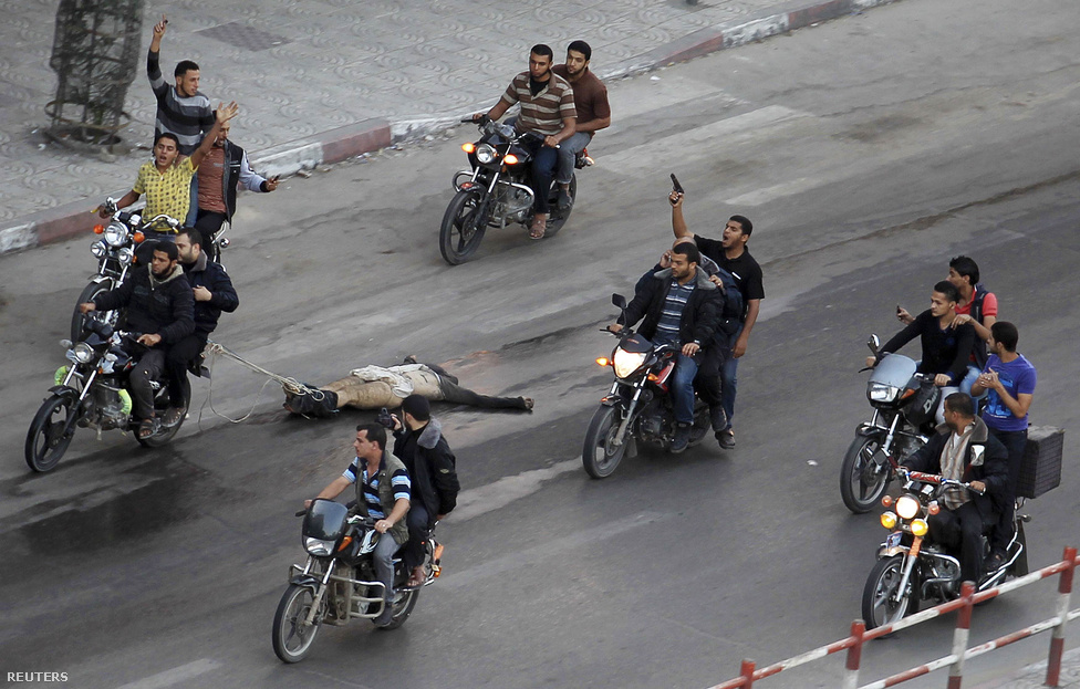 Motoruk után kötve hurcolnak végig egy férfit Gázában palesztin fegyveresek, november 20-án. A csoport tagjai hat embert lelőttek, a Hamasz rádiója szerint az áldozatok tetten ért izraeli kémek voltak.