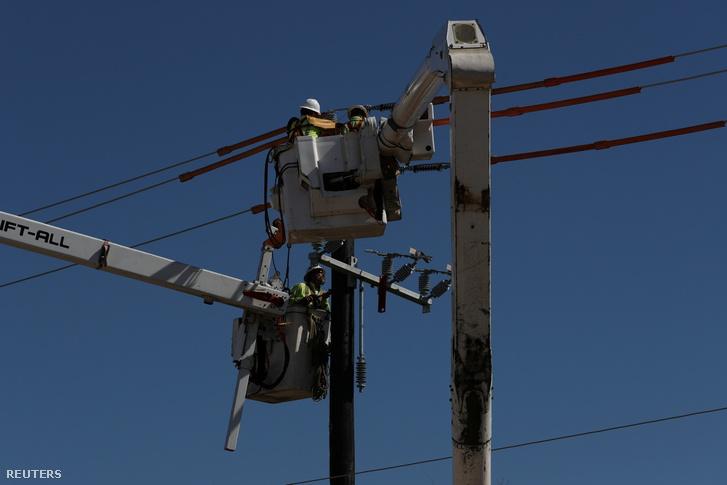 Egy villanyoszlopot erősítenek meg Houstonban a vihart követően, 2021. február 22-én