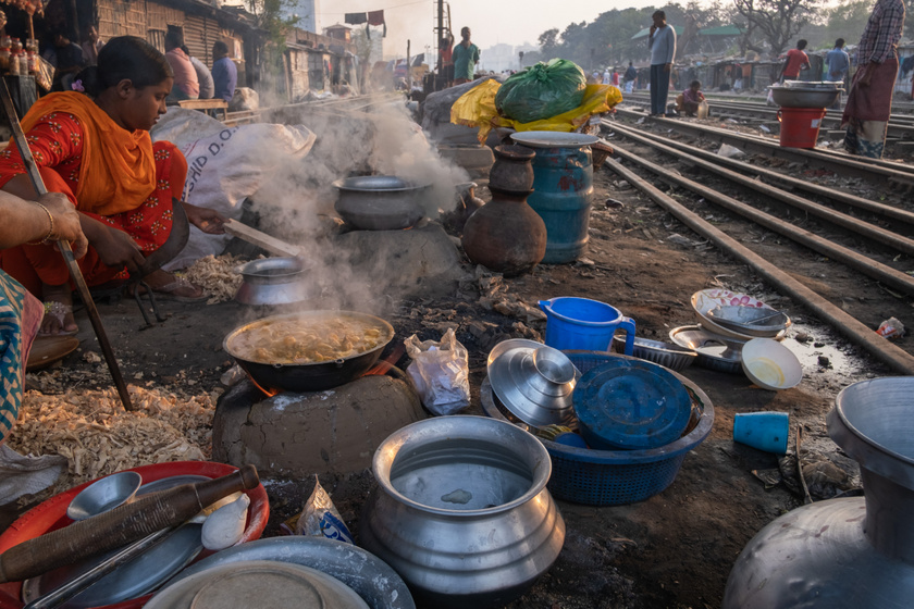 Dakka egyik nyomornegyedének lakói a vasútvonal mellett élnek közvetlenül a sínek mellett. Sokan közülük az ételeiket is itt készítik el.