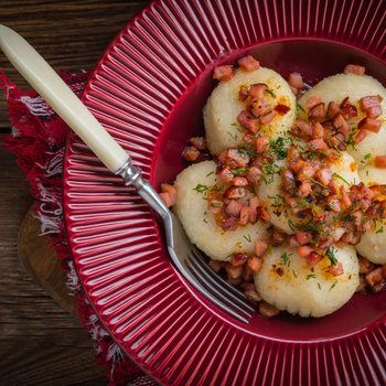 Hússal töltött krumpligombóc pirított szalonnával tálalva: a kartacze laktató, lengyel különlegesség