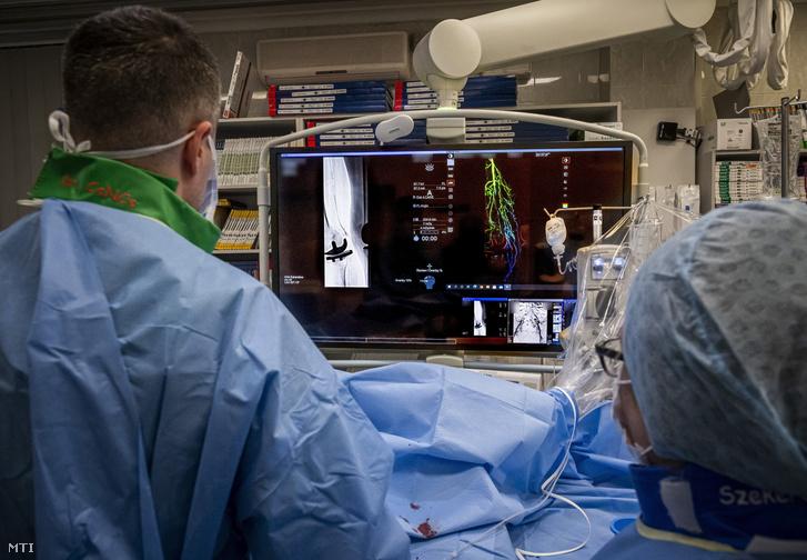 Egy intervenciós radiológus és műtősnő egy beteg lábának érfestéses vizsgálatát végzi a Semmelweis Egyetem Városmajori Szív- és Érgyógyászati Klinika perifériás intervenciós laboratóriumában 2021. január 29-én