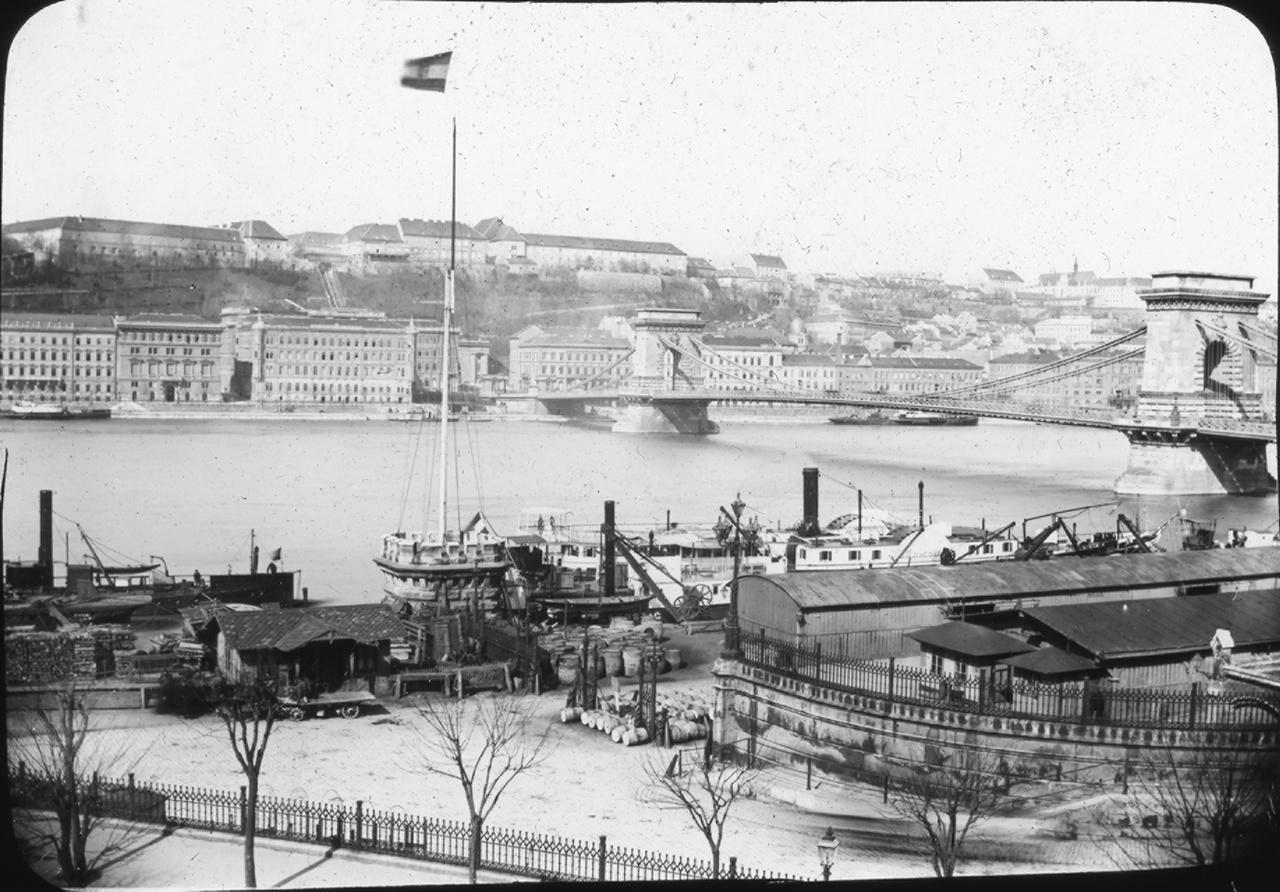 Látkép a Lánchíddal, a budai oldal házaival, a királyi palotával átépítése előtt, és a Duna-parti kikötőkkel, lerakatokkal