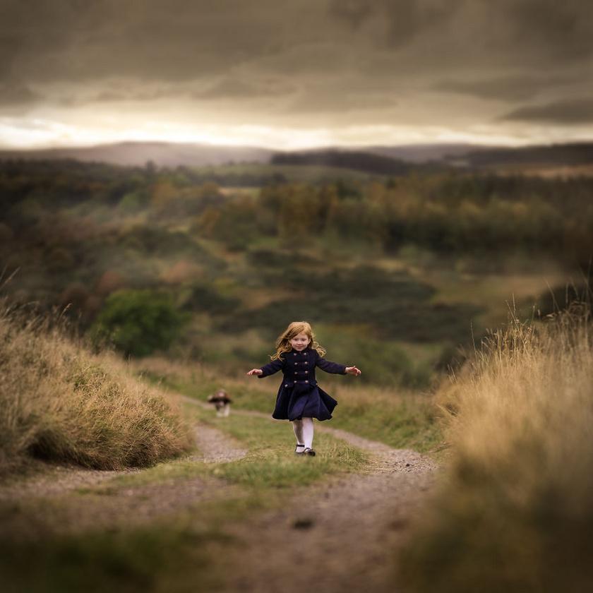 Skóciában egy kislány fut felfelé a dombon vidáman, mögötte a gyönyörű táj.
