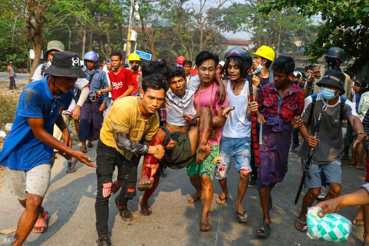 Egy férfit cipelnek biztonságos helyre Yangonban miután megsérült a tüntetésen 2021. március 14-én
