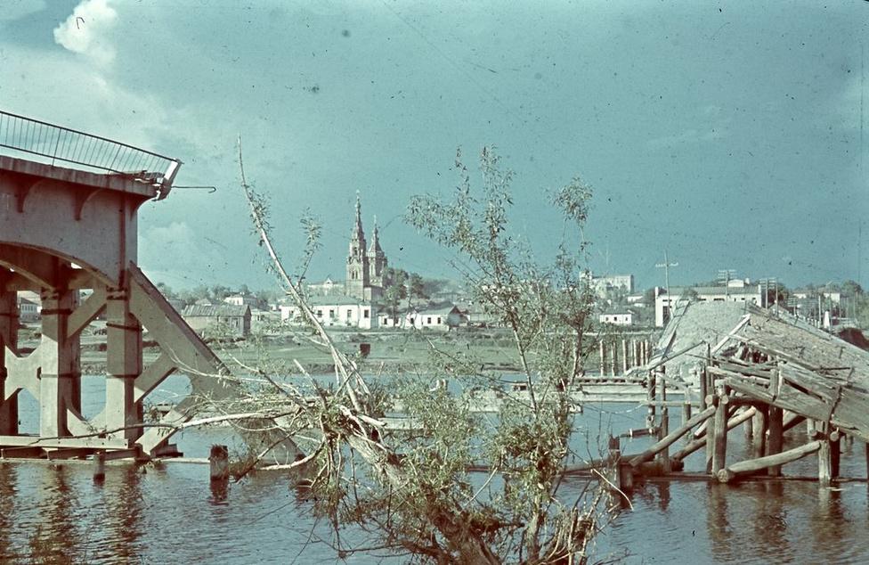 """A Don folyó lebombázott híddal, háttérben templom, ősz eleje. """"A doni magyar hadsereg mindinkább úgy érezte, hogy otthon már 'leírták'. A tél küszöbén áll, de az ehhez szükséges segítségből eddig semmit nem látott. Mindenki a váltást várja."""" (Lajtos Árpád: Emlékezés a 2. magyar hadseregre – 1942–1943)"""