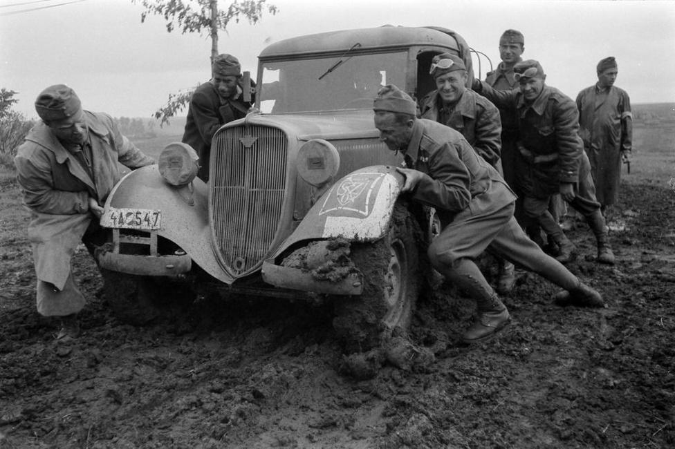 Az esős évszak beköszöntével egyre nehezebb volt az előrejutás, itt éppen egy elakadt Opelt próbálnak kitolni a sárból.