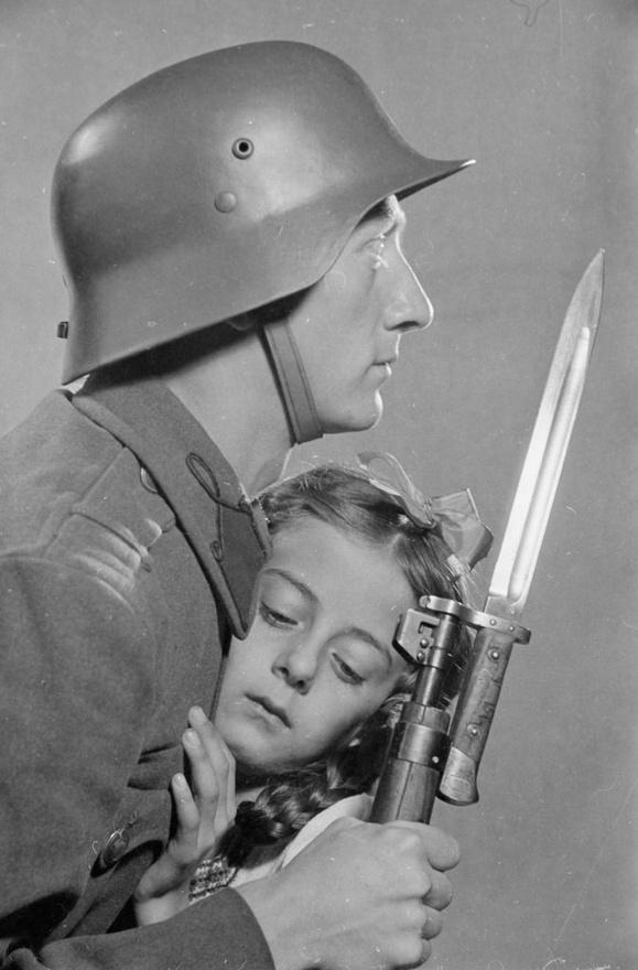Propandakép beállított kompozícióval. A magyar honvéd egy kislányt védelmez. A kislány a fényképész lánya, ifj. Konok Tamás testvére.