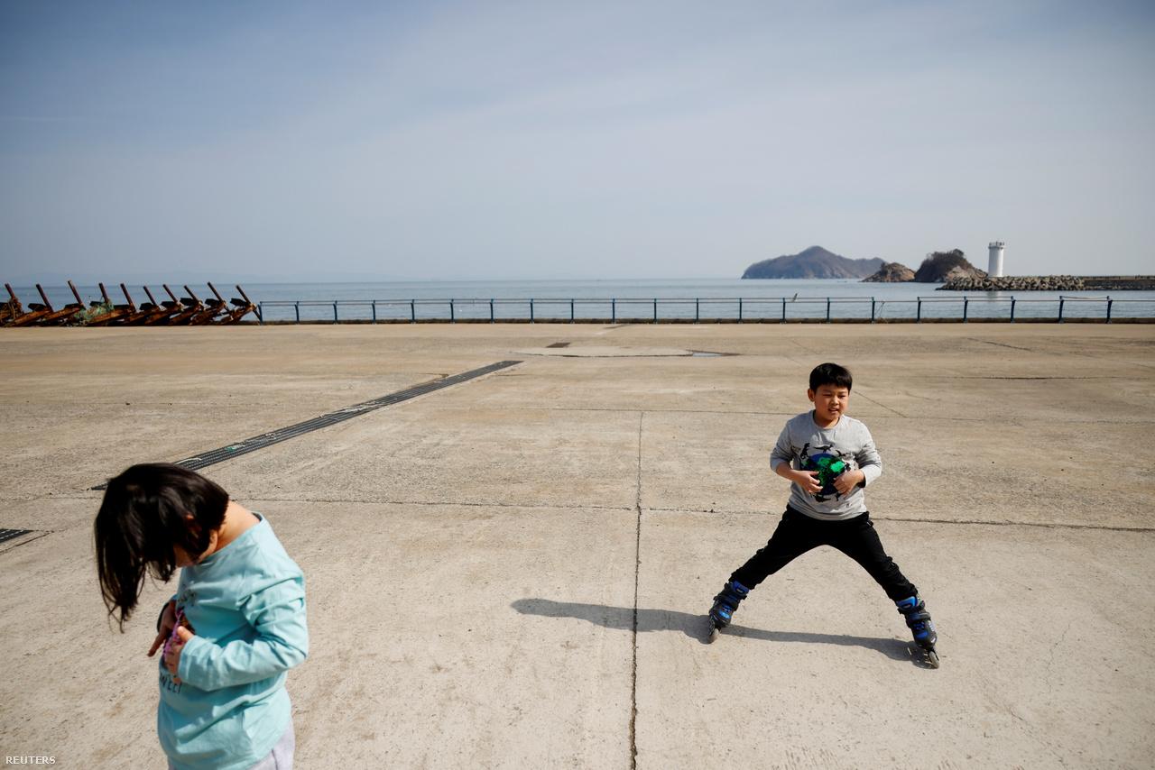 """A 10 éves Chan-hee kishúgával görkorizik a tengerparton. A Reuters stábjának a kisfiú elmondta, néha kicsit unja testvéreit. """"Jó lenne, ha több barátom lenne itt, mert akkor több lehetőségem lenne játszani″ – panszkodott Chan-hee. Nok-sziget, 2021.február 26-a."""