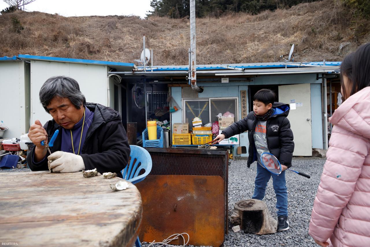 A 66 éves Kim Si-young azon kevesek egyike, akik az elvándorlás ellenére a szigeten maradtak. A fotón a gyerekek társaságában, frissen pirított osztrigát esznek. Nok-sziget, 2021. február 26-a.