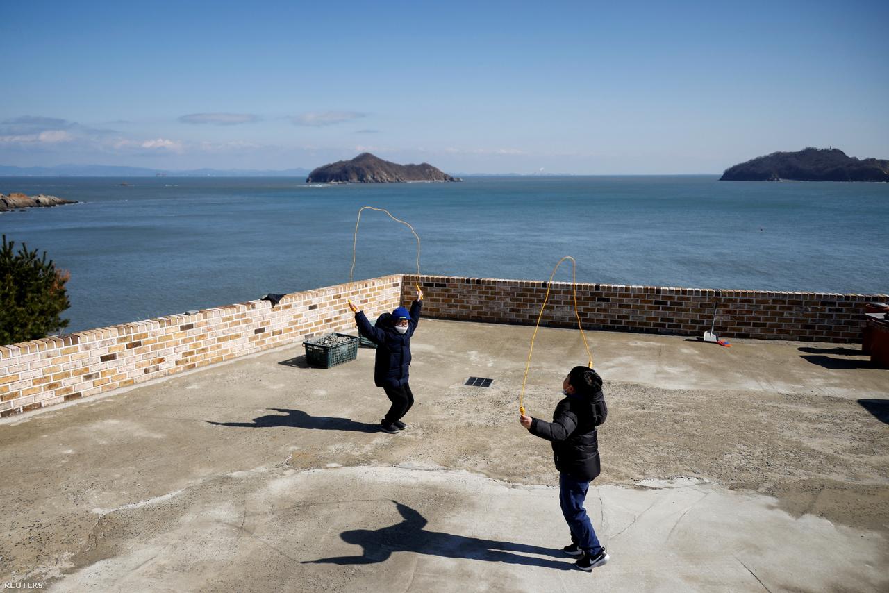 A 10 éves Lyoo Chan-hee és a 9 éves Kim Si-hu ugrókötelezik a szemeszter első tanítási napján. Nok-sziget, 2021. március 2-án. 2021.
