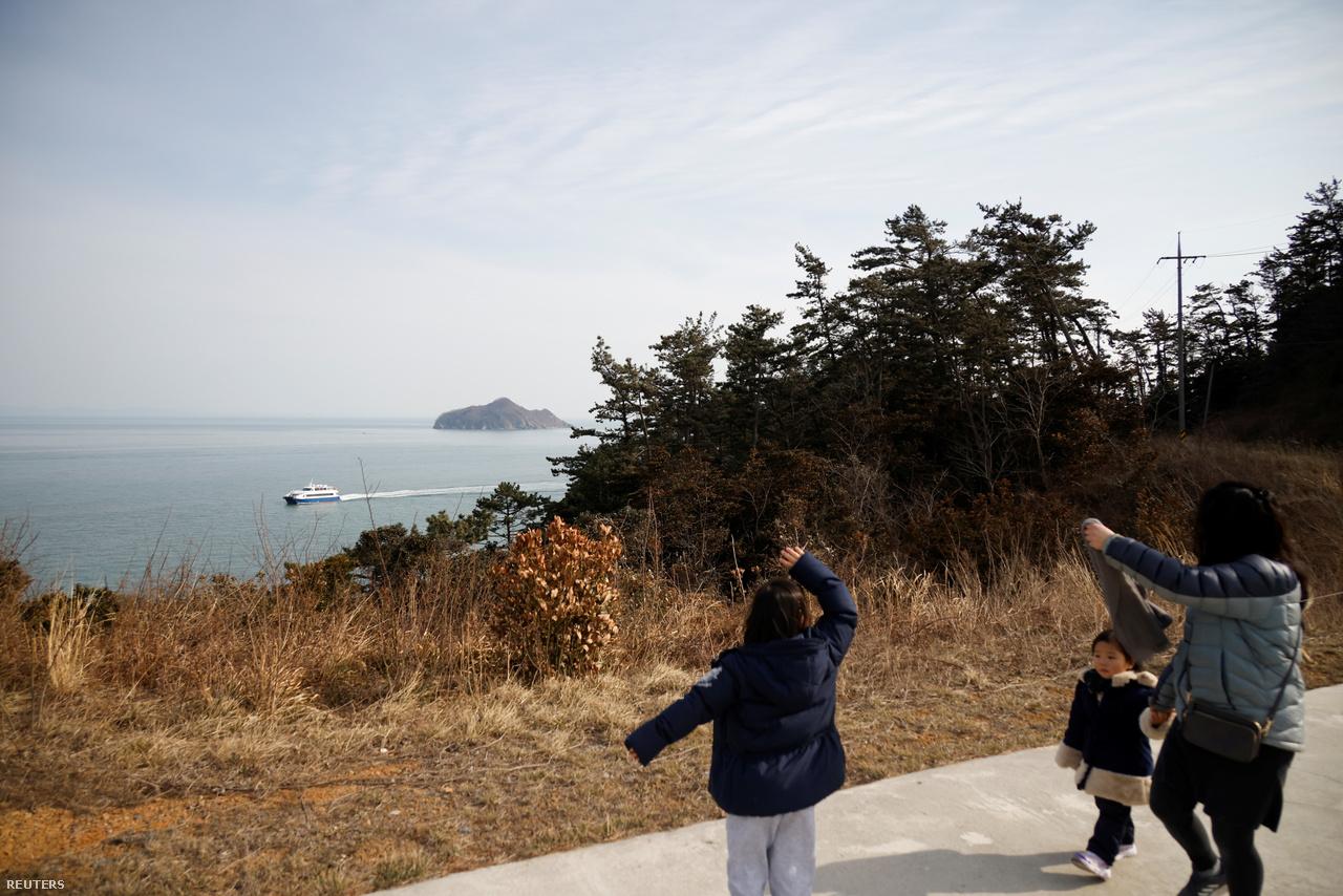 A hét éves Lyoo Chae-hee integet a Dél-Korea szárazföldjére visszainduló komp után. Nok-sziget, 2021. február 26-a.
