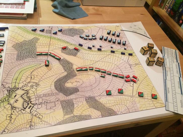 A Kriegsspiel 1824-es változatának rekonstruált kinézete. Jól láthatók a saját – kék és a közelebbi piros – ellenséges egységek, egy klasszikus katonai térképen elhelyezve. A kép szélén a mozgáshoz használt vonalzó látható, a jobb oldalt látható kockákat nem gördítették, hanem különböző számításokhoz (például mozgás, sebzés) szükséges adatokat tudták leolvasni róluk