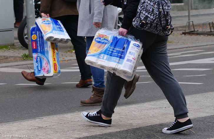 Koronavírus idején az emberek kéztörlőcsomagot visznek Berlinben 2020. március 18-án