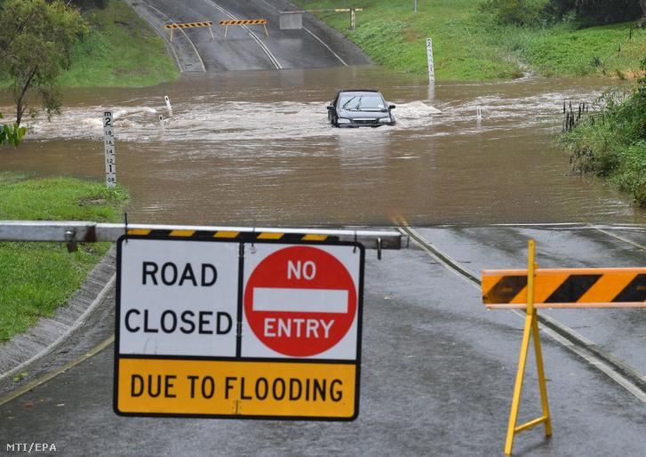 Személyautó hajt át a heves esőzések miatt vízzel elöntött úton a Queensland állambeli Gold Coastban 2021. április 6-án