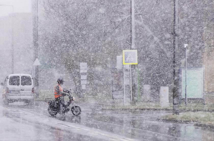 Motoros a hóesésben Nyíregyházán, a Sóstói úton 2021. április 6-án.