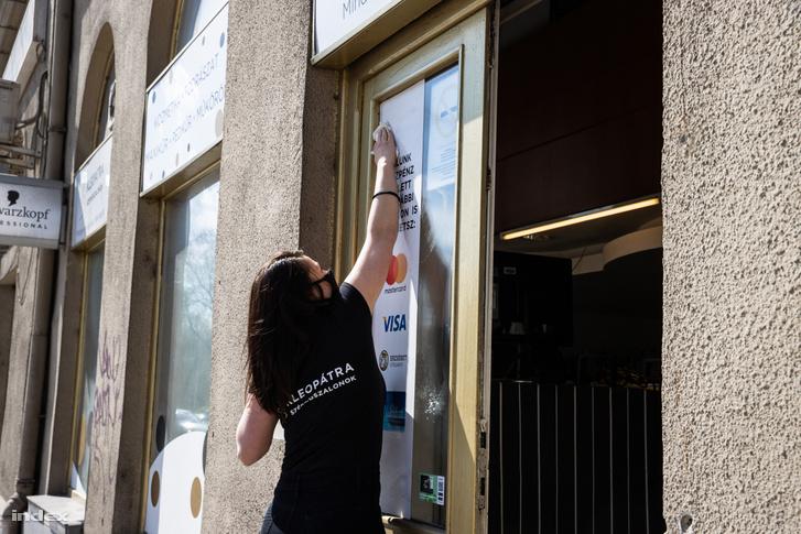 Takarítják a Kleopátra szépségszalon ablakát a nyitás előtt