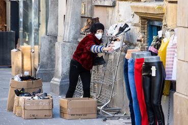 Egy cipőbolt tulajdonosa helyezi ki termékeit boltja előtt a budapesti Keleti Pályaudvarnál