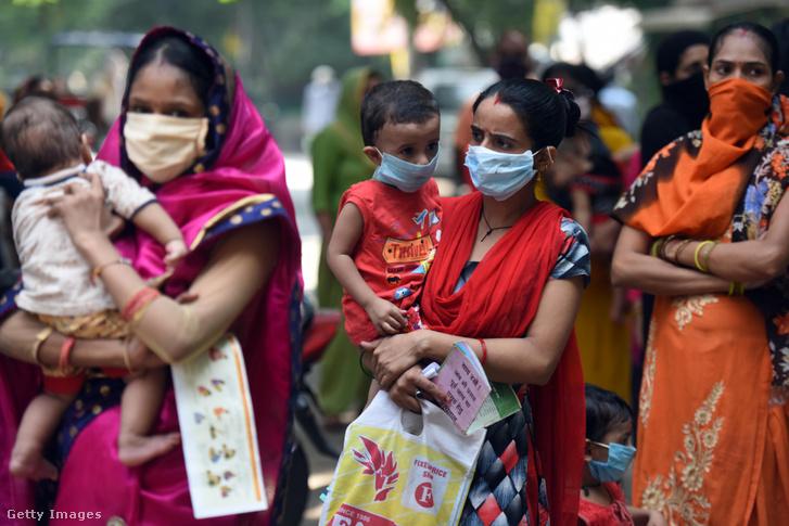 Indiai nők gyermekükkel oltásra várakoznak