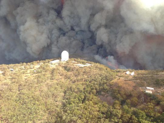 A tűzvész óriási füstfelhője az Siding Spring Observatory közvetlen közelében. A nagy kupola középen a 3,9 méteres Angol-Ausztrál Teleszkópé.