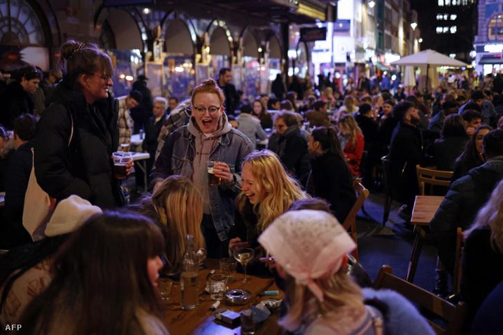 A londoni Soho körzetében található kocsmák és bárok előtti asztaloknál iszogatnak a fiatalok 2021. április 12-én