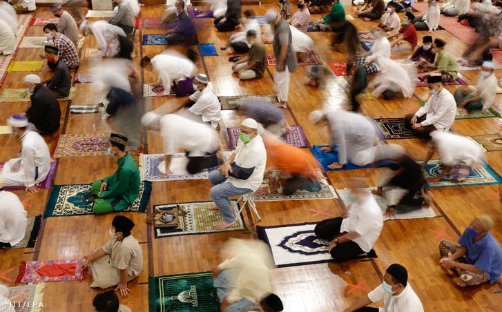 Muzulmán férfiak imádkoznak egymástól biztonságos távolságra a szent böjti hónap, a ramadán előestéjén az indonéziai Depok egyik mecsetében 2021. április 12-én