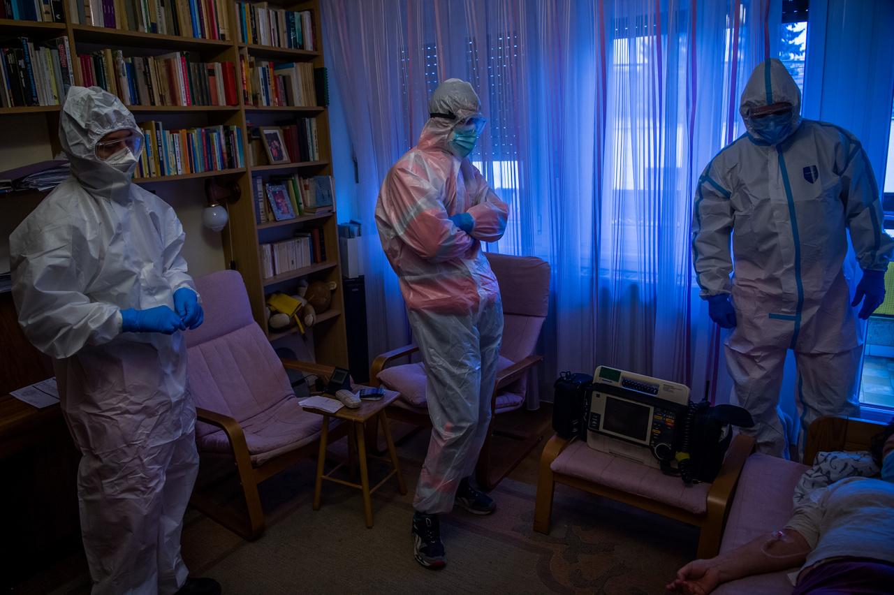 Képriport kategória 1. díj: A Covid-19 éve Magyarországon - Védőruhát viselő mentők koronavírussal fertőzött beteget látnak el otthonában 2020. november 25-én