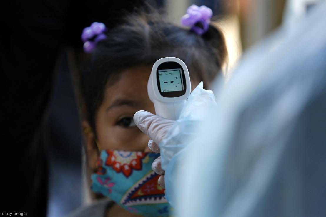 Egy bolíviai kislánynak megmérik a testhőmérsékletét 2020. április 28-án Bolívia fővárosában