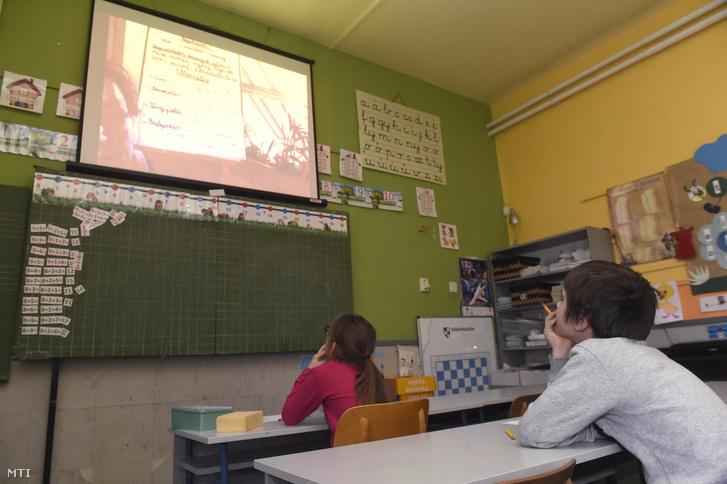Alsó tagozatos diákok figyelik a kivetítőn tanítójukat a Kőbányai Kertvárosi Általános Iskolában 2020. március 31-én