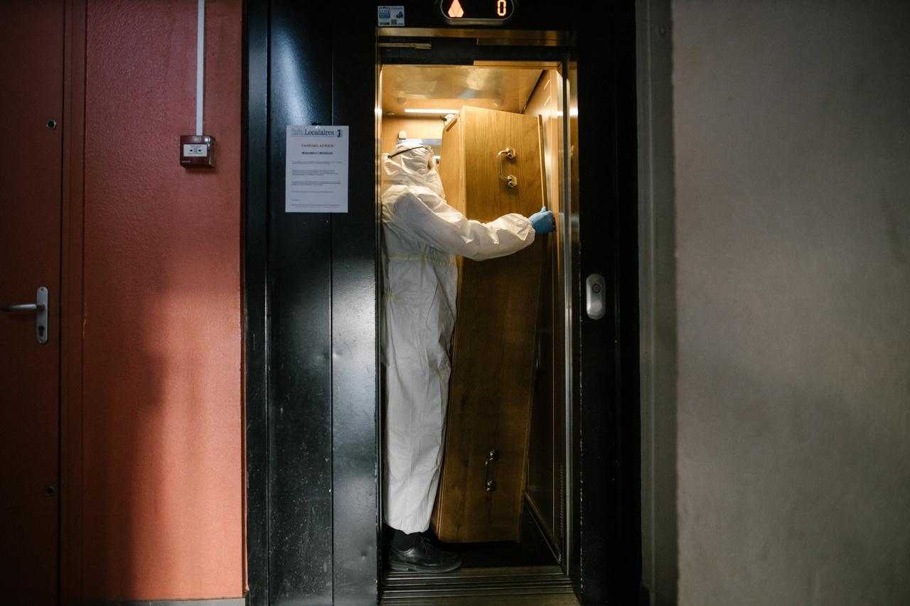 """Laurence Geai """"COVID-19 járvány Franciaországban"""" című sorozata harmadik helyezést ért el az általános hírek (sorozat) kategóriában. A képen egy koporsóba helyezett holttestet szállítanak el liften egy társasház ötödik emeletéről Párizs egyik külvárosában, Pantinban."""