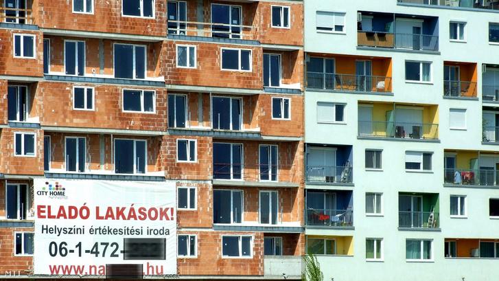 Új építésű eladó lakásokat hirdet egy hatalmas plakát a még burkolatlan lakótömb falán 2013. április 21-én