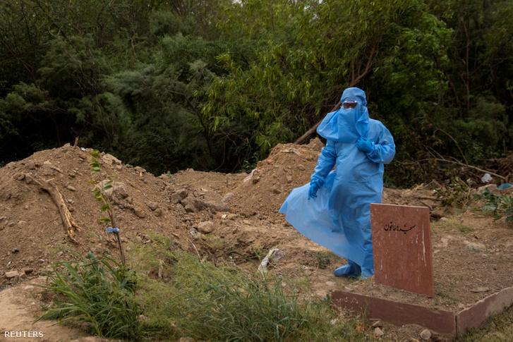 Egy koronavírusban meghalt indiai ember rokona vára temetés kezdetére egy sír mellettÚj-Delhiben április 16-án