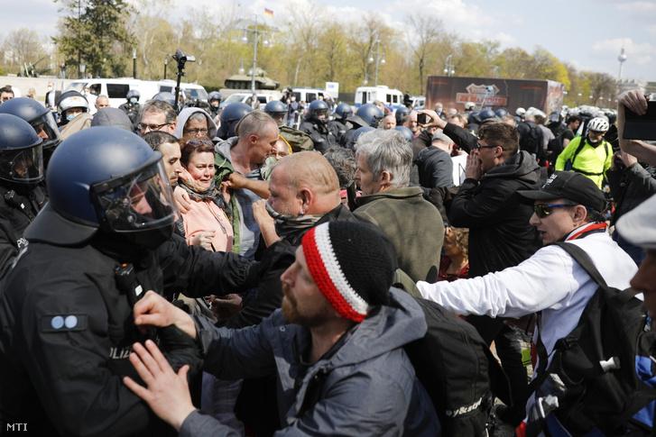 A koronavírus-járvány megfékezését célzó kormánypolitika ellen tüntetők és rohamrendőrök Berlinben 2021. április 21-én