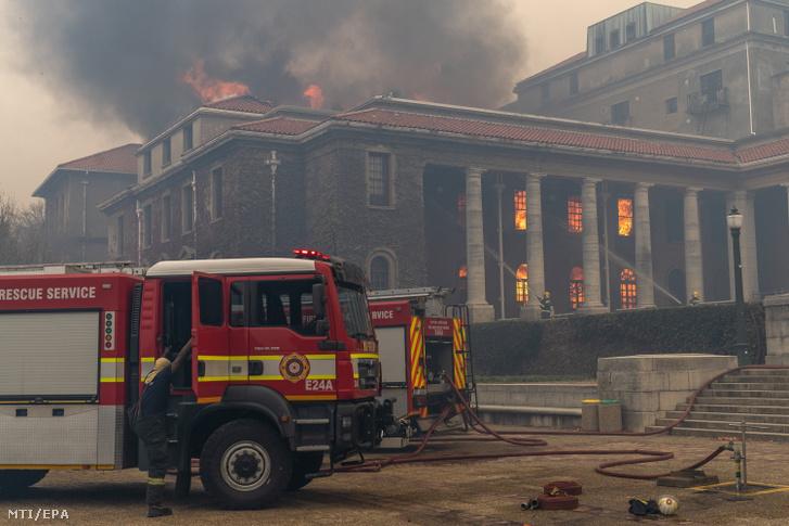 Tűzoltók küzdenek a lángok megfékezésén a fokvárosi Tábla-hegy lábánál fekvő Jagger egyetemi könyvtárnál 2021. április 18-án