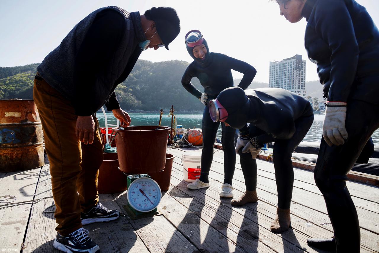 Dzsin, Vu és Kim Mjungszun szemlélik a zsákmányt 2021. március 30-án Kodzse partjainál.