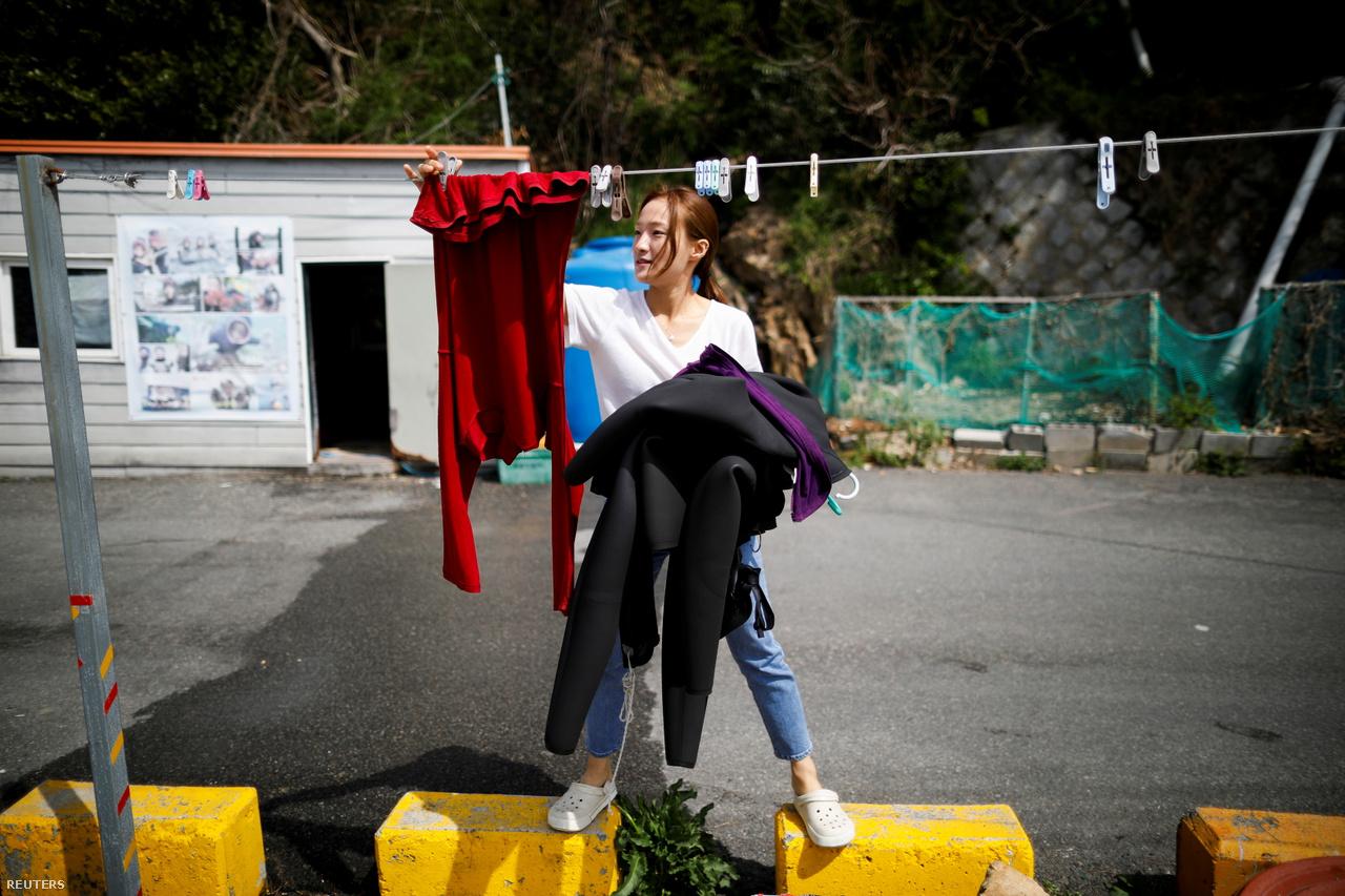 A 28 éves Dzsin szárítja a búvárruháját. A klímaváltozás ellehetetlenítheti ezt a tradicionális foglalkozást.