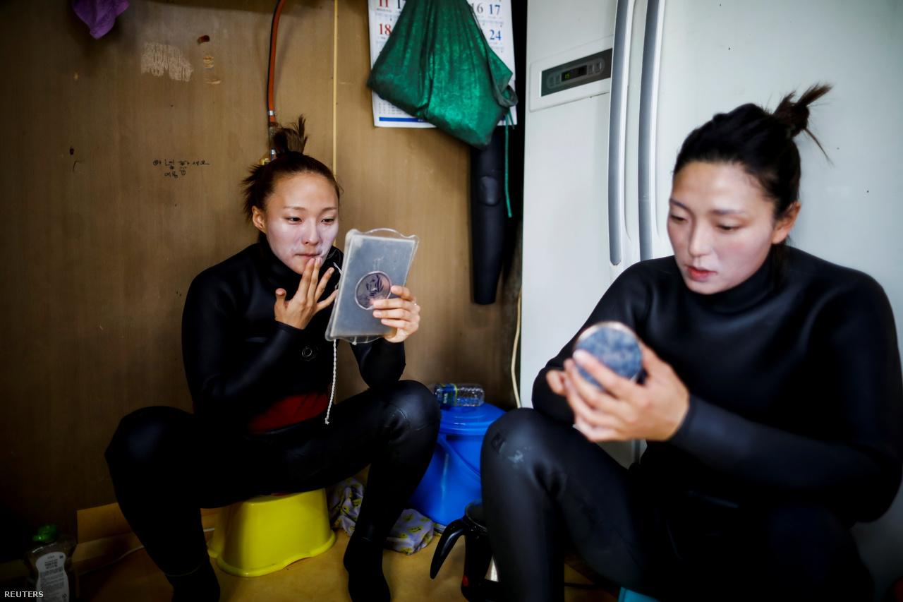 Dzsin és Vu környezetbarát napkrémmel kenik be az arcukat, mielőtt munkába mennek Kodzse szigetén 2021. március 31-én. Ők ketten a legfiatalabb henyók közé tartoznak. A legtöbb henyo már elmúlt 70 éves. Dzsin és Vu létrehoztak egy You Tube-csatornát, amelyen bemutatják a tengeri asszonyok életét. A legnépszerűbb videójukat már 600 000-en látták.