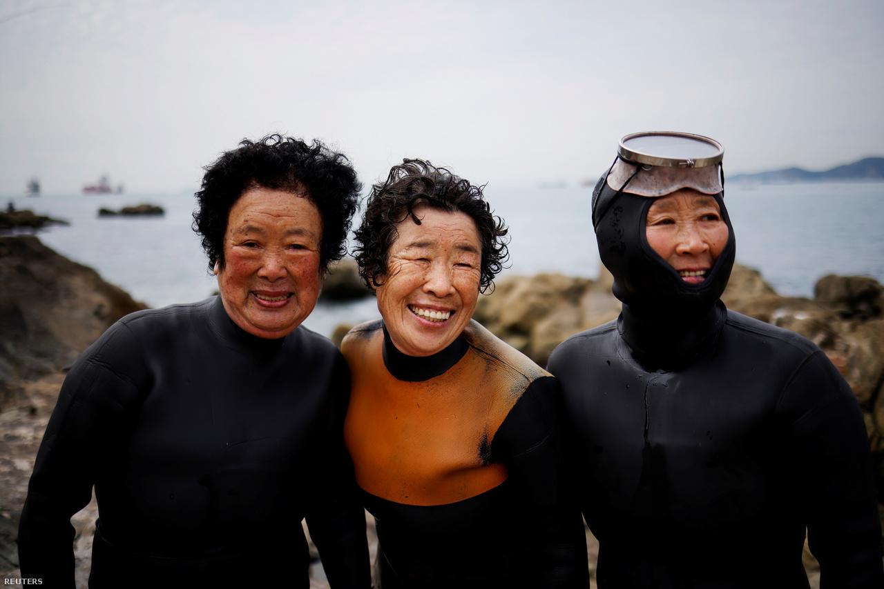 Három idős henyo, a 84 éves Dzsung Szunja, a 74 éves Ko Kumszun és a 69 éves Jun Jonok mosolyognak a fényképezőgép lencséjébe Puszan mellett 2021. április 6-án.