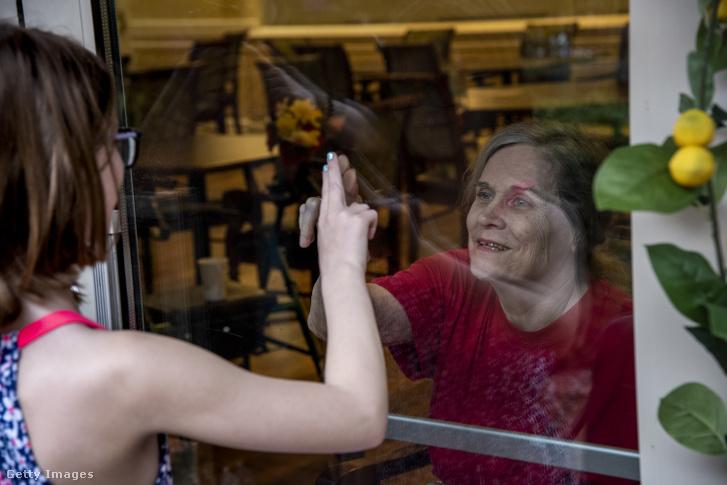 A koronavírus-járvány miatt a családtagok üvegablakon keresztül láthatják egymást