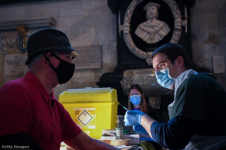 Alkalmazottak a Pfizer koronavírus elleni vakcinát adják be egy betegnek a Salisbury székesegyházában létrehozott oltási központban 2021. január 20-án Angliában
