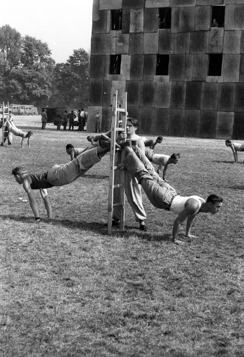 Margitsziget, park a Dózsa teniszstadionnál, önkéntes tűzoltók csapatai gyakorolnak a bemutató előtt, 1958. Az első tűzoltók nem hivatásosok voltak. Az önkéntes tűzoltók a közösség tagjaiból szerveződtek – mind a kollégiumok, céhek, gyárak, majd falvak és városok védelme érdekében. Egy 1956-os törvény értelmében minden közösségnek fel kell állítania önkéntes tűzoltóságot. Napjainkban az 1996-os törvény szerint az önkéntes tűzoltók egyesületi formában működhetnek, melyet az állam által biztosított forráson túl az önkormányzatok is támogathatnak. Jelenleg közel hétszáz önkéntes tűzoltó egyesület működik Magyarországon a hivatásos parancsnokságok mellett, melyekre szükség is van, hiszen a tűzesetek rendkívül gyakoriak, átlagosan óránként keletkeznek lakástüzek. A legtöbb lakástűz eredete emberi mulasztás, ezek közül kiemelkedő a rossz minőségű fűtőtestek és elektromos berendezések meghibásodása, a tűzhelyen felejtett olaj és a lakásban való dohányzás okozta tüzek. A lépcsőházakban és az e