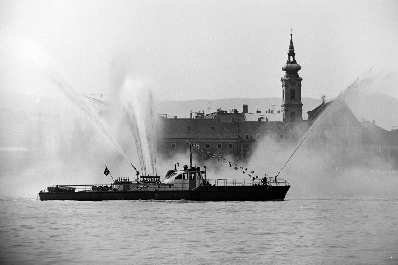 Tűzoltóhajó az augusztus 20-i légiparádén, 1970.A tűzoltóhajók békeidőben a parádé részét képezik, de eredeti hivatásuk a szárazföldről nem megközelíthető vagy vízen – ilyen például a hajókon keletkezett tüzek oltása. Az első szivattyúhajókat, Gigant és Pluto névre keresztelték, az Osztrák-Magyar Monarchia Császári és Királyi Haditengerészet részére gyártották le 1877-1878-ban, és feltehetően ezek voltak az első tűzoltóhajók is egyben. A legelső hazai gyártmány a Szent Flórián néven Angyalföldön vízre bocsátott hajó, melynek feladata a tűzoltás és műszaki védelem volt. 1947-ben Vörös Október névre keresztelték át, és 1961-ig ezen a néven teljesített szolgálatot. A képen látható jármű a T1 tűzoltóhajó, '61-ben vette át a szolgálatot a Vörös Októbertől. 1982-ig tartó szolgálata alatt változatos feladatokat látott el öt fős tűzoltó személyzetével. Hajótüzek, partmenti tüzesetek mellett árvizeknél is bevetették. Jelenleg szolgáló tűzoltóhajó Magyarországon a Szent Flórián nevet kapta; a 13 méter hosszú