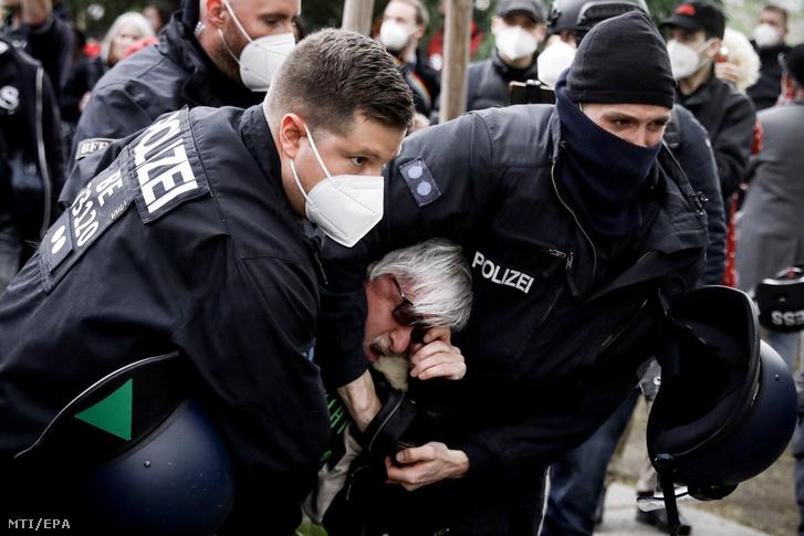 A koronavírus-járvány megfékezésének érdekében bevezetett korlátozások ellen tiltakozót vesznek őrizetbe rendőrök Berlinben 2021. május 1-én
