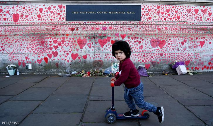 A koronavírus-járvány brit áldozatai tiszteletére kialakított emlékfal előtt rollerezik egy kisfiú London belvárosában 2021. április 27-én. A piros szíveket március 29-én kezdték el felrajzolni a falra az elhunytak hozzátartozói.