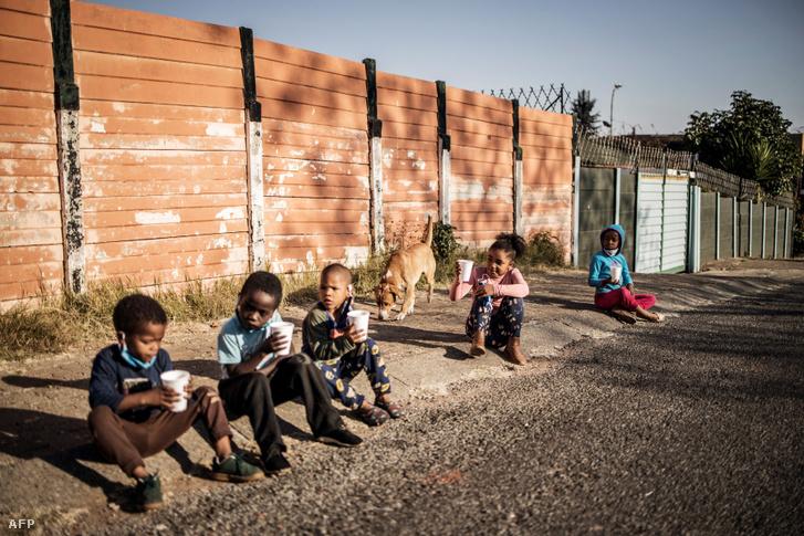 Gyerekek a földön ülve eszikareggelit Dél-Afrikában 2020. május 23-án