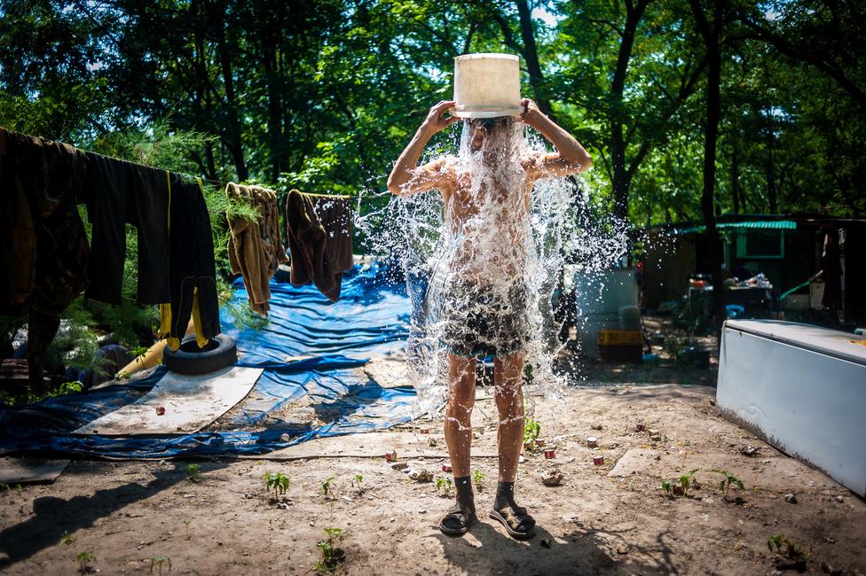 Társadalomábrázolás (egyedi) harmadik hely Kallos Bea (MTVA/MTI) - Zuhany Robi egy vödör esővízzel hűsíti magát a forróságban a Terebes utcai erdőben. Robi 4 éve csatlakozott az akkor már ott élő Zoltánhoz és Mónikához.